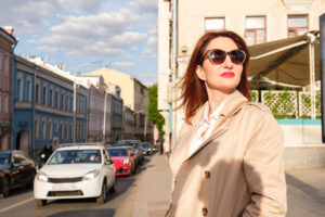 what to wear today, woman in long coat and sunglasses standing on street